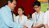 SGGP Editor-in-Chief Nguyen Tan Phong gives the scholarships to students at the ceremony (Photo: SGGP)