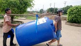 Poor people receive water containers (Photo: SGGP)