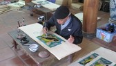 Artisan Nguyen Dang Che finishes a Dong Ho painting called Ca Chep Trong Trang (Moonlight Carp) (Photo: VNA)