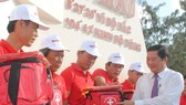 Deputy Chairman of Ca Mau People's Committee Than Duc Huong gives flags to fishermen (Photo: SGGP)