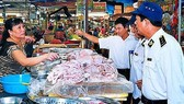 Inspectors visit a food booth in a tradiational market (Photo: SGGP)