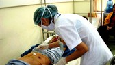 A medical worker is providing treatment to a patient after operation (Photo: SGGP)