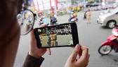 A citizen films a on-duty traffic police in HCM City. — Photo luatvietnam.vn