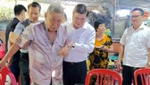 Chairman Phong leads resident Hai by the hand (Photo: SGGP)
