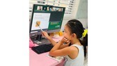 Second grader Pham Bao Thien Kim is taking part in an online lesson at home. (Phot: SGGP)