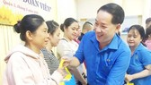 A representative of HCMC Federation of Labor is delivering financial aid to unemployed people due to the Covid-19 pandemic. (Photo: SGGP)