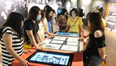 Visitors are excited with interactive touchscreen. Museums apply digital technologies to attract visitors (Photo: SGGP)