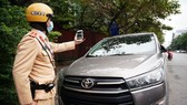 The police officer takes photos as an evidence of an illegally parking car (Photo: SGGP)