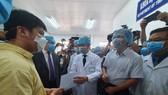 Bác sĩ Nguyễn Tri Thức, Giám đốc Bệnh viện Chợ Rẫy trao giấy xuất viện cho bệnh nhân Li Zichao (áo vàng)
