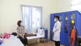 Nhân viên y tế giữ khoảng cách an toàn khi tiếp xúc với người cách ly ảnh: HOÀNG HÙNG