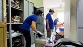 Các thầy cô Trường ĐHQG TPHCM thu dọn toà nhà Công đoàn nhường chỗ cho những người cách ly mới . Ảnh: HOÀNG HÙNG