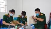 Các bác sĩ Bệnh viện Dã chiến 2.3 tận dụng thời gian sau huấn luyện để làm ra sản phẩm nón kính phòng hộ. ẢNH: TRẦN CHÍNH