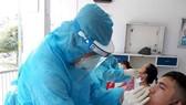 Nhân viên y tế lấy mẫu xét nghiệm cho công nhân tại Khu chế xuất Tân Thuận (quận 7)