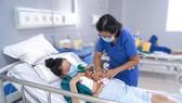 Bác sĩ đang thăm khám cho mẹ con sản phụ  ẢNH: BVCC