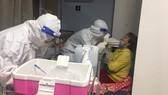Nhân viên y tế Bệnh viện Gia An 115 lấy mẫu xét nghiệm cho thân nhân người bệnh