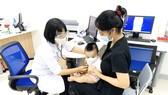 Người dân đưa trẻ đi tiêm chủng tại VNVC Bình Phước