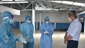 Thứ trưởng Bộ Y tế Nguyễn Trường Sơn thăm hỏi động viên nhân viên y tế lấy mẫu xét nghiệm cho người dân tại phường 25, quận Bình Thạnh.  Ảnh: KHÔI NGUYÊN