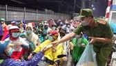Lực lượng công an tổ chức phát cơm, bánh mì, sữa và nước uống miễn phí cho người dân đang trên đường về quê