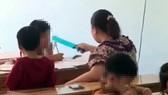 Người phụ nữ dùng thước kẻ đánh học sinh khi đang dạy chữ. Ảnh cắt từ clip