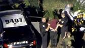 Tay súng (áo đỏ sẫm) bị cảnh sát bắt giữ sau vụ xả súng. Ảnh: REUTERS