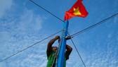 Ngư dân kiểm tra lại dây buộc Quốc kỳ trước khi cho tàu ra khơi. Ảnh: NLĐ