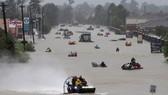 Cư dân sử dụng thuyền sơ tán khỏi vùng nước lụt do siêu bão Harvey gây ra. Ảnh: REUTERS