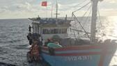 Các nhân viên tàu SAR 412 đưa xuồng cao su tiếp cận tàu cá và chuyển ngư dân Lê Thanh Hải sang tàu SAR 412 đưa về đất liền cấp cứu