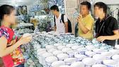Khách chọn mua chén đĩa tại Làng gốm Bát Tràng (Hà Nội)