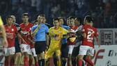 Các cầu thủ Thanh Hoá và TPHCM cản thủ môn Thành Thắng tiến đến gây sự với trợ lý trọng tài Nguyên Thành. Ảnh: MINH HOÀNG