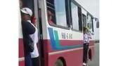 Hình ảnh các em học sinh đu bám trên của xe buýt rất nguy hiểm.