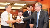 HCMC Party Chief Nguyen Thien Nhan shakes hands with an overseas Vietnamese at the meeting on January 24 (Photo: SGGP)