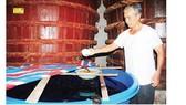 A traditional fish sauce maker checks the quality of fish sauce. (Photo: SGGP)