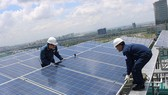 Workers install solar panels on the roof of a building. (Photo: SGGP)