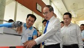 HCMC Party Chief Nguyen Thien Nhan learns about Vietnamese branded products (Photo: SGGP)