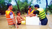 A boy receives food from rescue force in the Mekong Delta (Photo: SGGP)