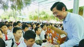 Journalist Nguyen Nhat, Deputy Editor-in-chief of SGGP Newspaper, gives students presents (Photo: SGGP)