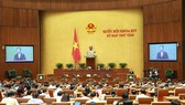 Minister of Industry and Trade Tran Tuan Anh answers deputies' questions (Photo: VNA)