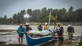 Fishermen carry a boat to higher ground in Baybay, eastern Samar on December 24 after typhoon Phanfone hit the central Philippines (Source: AFP)
