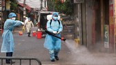 Medical workers spray steriliser in Ha Loi Village where two COVID-19 patients live (Photo: VNA/VNS)