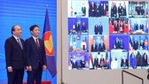 Vietnamese Prime Minister Nguyen Xuan Phuc (L) and Minister of Industry and Trade Tran Tuan Anh, together with leaders of other RCEP member countries, witness the pact signing via videoconference on November 15 (Photo: VNA)