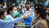 Medical workers check body temperature for police officers in Bangkok, Thailand (Photo: AFP/VNA)