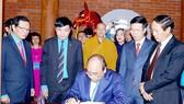 Thủ tướng Nguyễn Xuân Phúc ghi sổ lưu niệm tại Nhà tưởng niệm đồng chí Nguyễn Đức Cảnh.  Ảnh: TTXVN