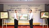 Bộ trưởng Bộ Thông tin và Truyền thông Nguyễn Mạnh Hùng (phải) tặng bức tem cho Trưởng Ban Tuyên giáo Trung ương Võ Văn Thưởng. Ảnh: TTXVN