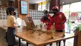 Một quán ăn trên địa bàn quận 8 kê bàn khoảng cách 2m giữa khách và nhân viên  nhằm phục vụ cho những món mang về. Ảnh: HOÀNG HÙNG