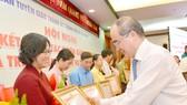 Bí thư Thành ủy TPHCM Nguyễn Thiện Nhân trao bằng khen cho các tập thể đạt thành tích xuất sắc trong công tác tuyên giáo. Ảnh: VIỆT DŨNG