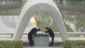 Thị trưởng Matsui Kazumi (phải) nhận và đặt danh sách nạn nhân của vụ ném bom vào bên trong bia tưởng niệm. Ảnh: AP