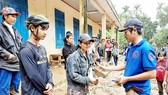 Thầy giáo Nguyễn Trần Vỹ (bìa phải) trao tặng tiền hỗ trợ bà con  xã Trà Leng, Quảng Nam, bị bão số 9 làm hư hại tài sản