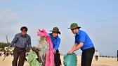 Ông Phan Ngọc Thọ, Chủ tịch UBND tỉnh Thừa Thiên - Huế (giữa) đang dọn rác trên bãi biển Thuận An.
