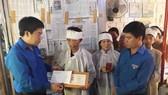 """a mẹ đón nhận và nâng niu Huy hiệu """"Tuổi trẻ dũng cảm"""" do Trung ương Đoàn TNCS Hồ Chí Minh truy tặng cho người con trai quên mình cứu người"""