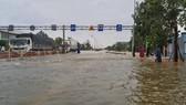 Quốc lộ 1A qua địa bàn thị xã Hương Trà bị ngập sâu khiến người và phương tiện tham gia giao thông gặp khó khăn